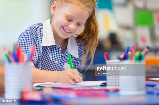 schoolgirl working at a desk. - workbook stock photos and pictures