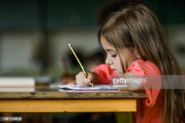 schoolgirl writing a dictation during a class in elementary school. - one girl only stock pictures, royalty-free photos & images