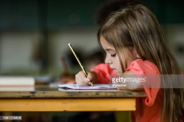 schulmädchen schreiben ein diktat während einer klasse in der grundschule. - schulheft stock-fotos und bilder