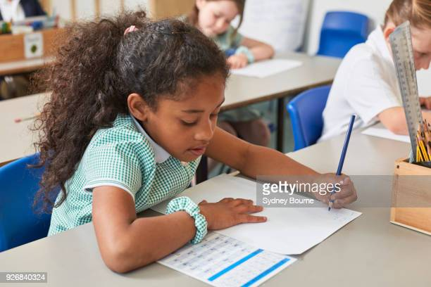 Schoolgirl writing at classroom desk in primary school lesson