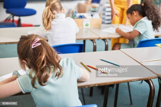schoolgirl writing at classroom desk in primary school lesson, rear view - elementary school stock pictures, royalty-free photos & images