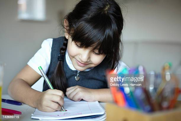 schoolgirl writing at desk - homework stock pictures, royalty-free photos & images