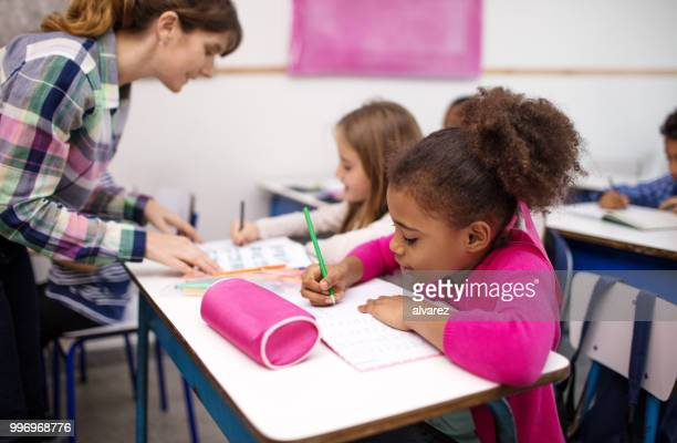 schoolgirl writing in book at desk in classroom - pencil case stock photos and pictures