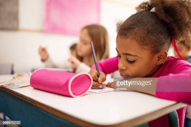 schoolgirl writing in book at desk - pencil case stock photos and pictures