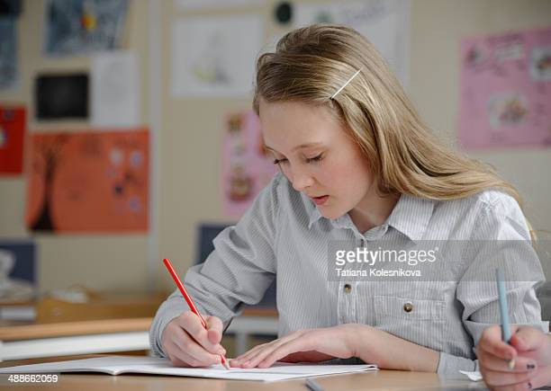 schoolgirl writing in classrom - hairpin stock pictures, royalty-free photos & images