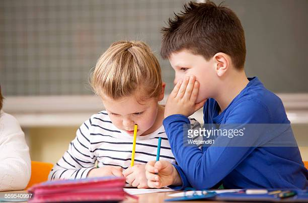 Schoolgirl writing while boy is whispering in here ear