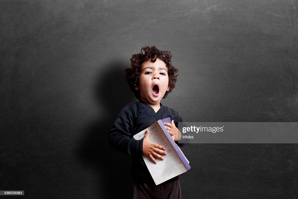 Schoolgirl yawning in classroom during study : Stock Photo