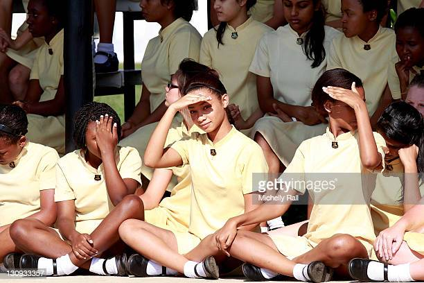 Schoolgirls await the arrival of Charlene Wittstock future Princess of Monaco to attend the ribbon cutting ceremony for the opening of the school...