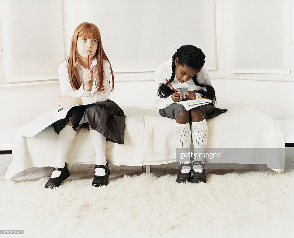 Schoolgirls Doing Their Homework Sitting on a Bed : Stock Photo
