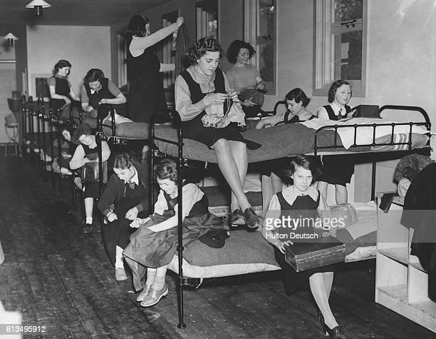 Schoolgirls evacuated from Leyton settle into a dormitory at a school camp near Farnham in Surrey England April 1940 | Location near Farnham England...