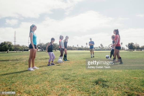 schoolgirls face to face kicking soccer ball to each other on school sports field - kick line stock photos and pictures