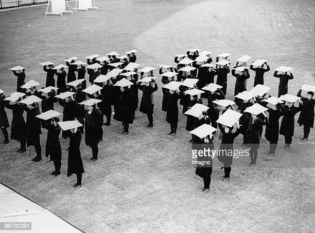 Schoolgirls from Lowestoft practicing for coronation show beeing showed how to hold the flags above their heads to form a design England Photograph...