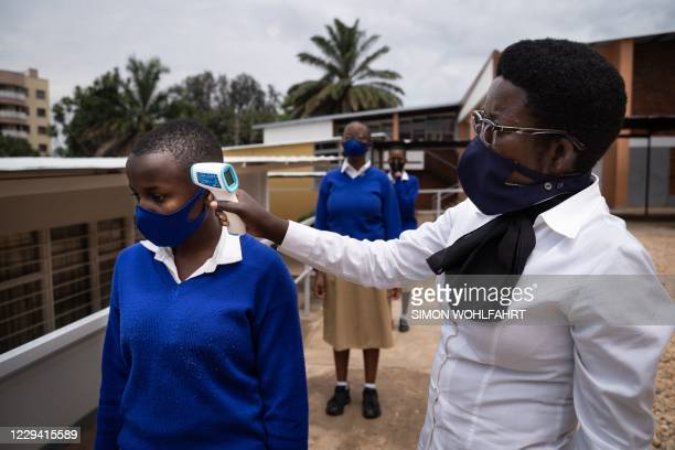 Schoolgirls get their temperature measured before the first class in about eight months at at Lycee Notre dame de Citeaux school in Kigali, Rwanda,...