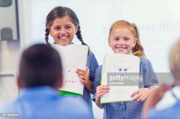 Schoolgirls giving a presentation in school uniform.