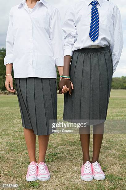 schoolgirls holding hands - black skirt stock pictures, royalty-free photos & images