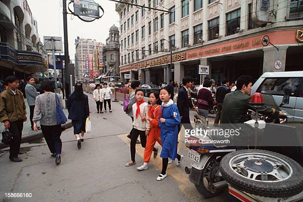 Schoolgirls in uniform cross the busy Nanjing Road All these children are unlikely to have brothers or sisters as China has a strict one child family...
