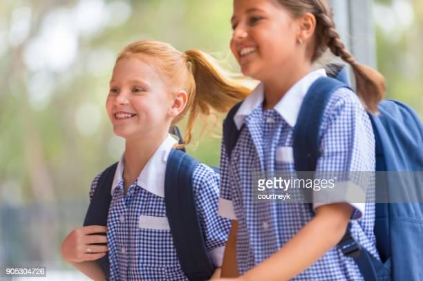 Schoolgirls in uniform with back pack.