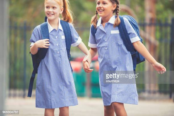 schoolgirls in uniform with back pack. - schoolgirl stock pictures, royalty-free photos & images