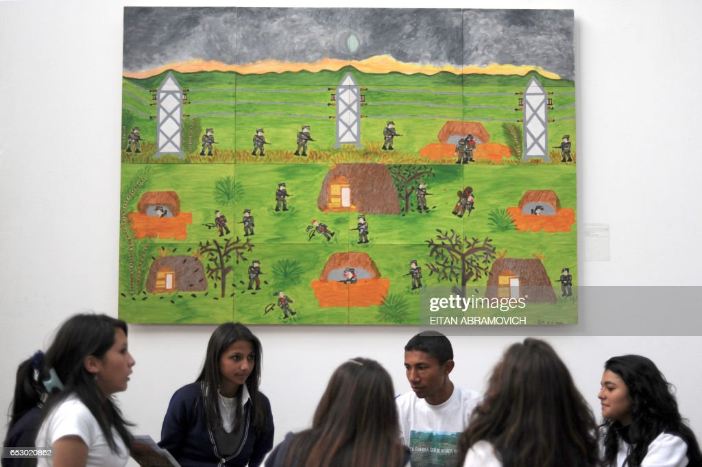Schoolgirls listen to a guide (4th-L) close to a painting from the exhibit 'The War We Haven't Seen' at Bogotas Museum of Modern Arts, on October 28, 2009. The exhibit gathers 90 paintings by about 80 former combatants of Colombias four-decade-old conflict. AFP PHOTO/Eitan Abramovich /