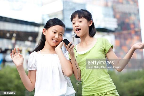 Schoolgirls listening to MP3 player together