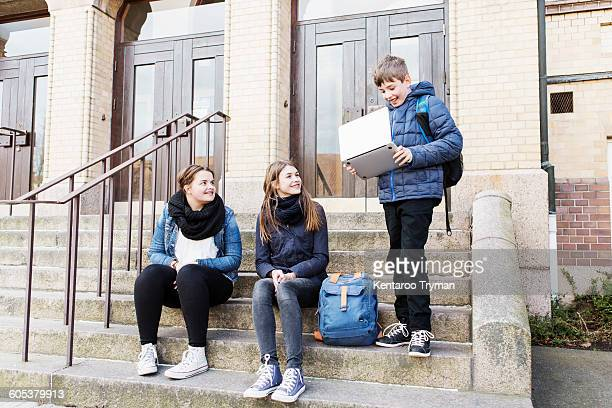 Schoolgirls looking at boy holding laptop on steps