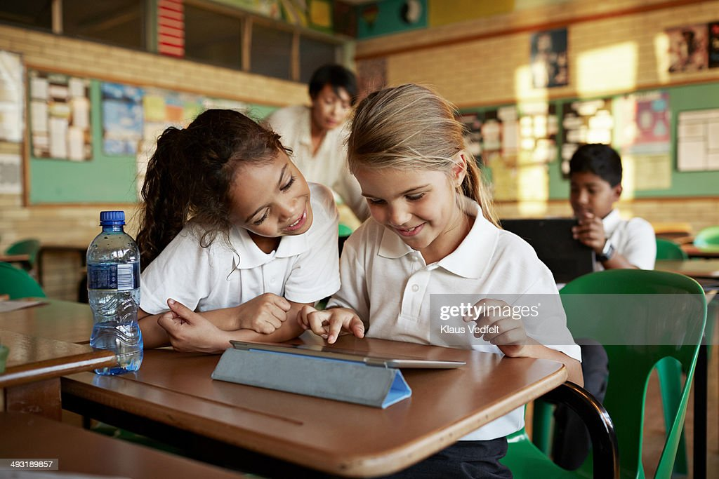 Schoolgirls looking at tablet togther and smiling : Stock Photo