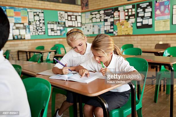 Schoolgirls looking together in book in class