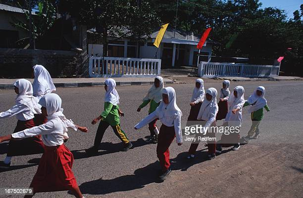 Schoolgirls march in front of a former UN office which is now an office of Kopassus the Indonesian military police In 1999 two UN aid workers working...