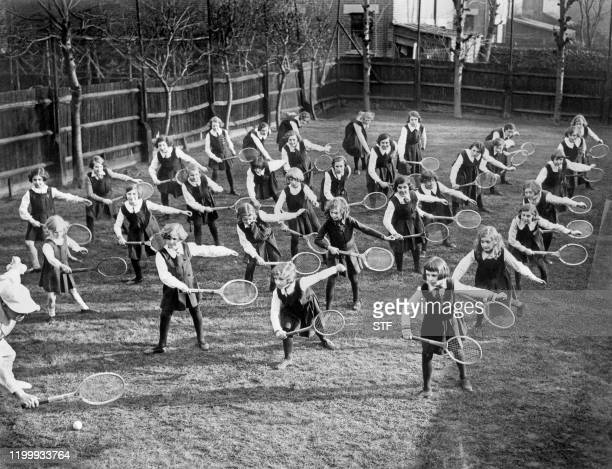 Schoolgirls of the Glenarm college in Ilford are taking tennis lessons in 1935