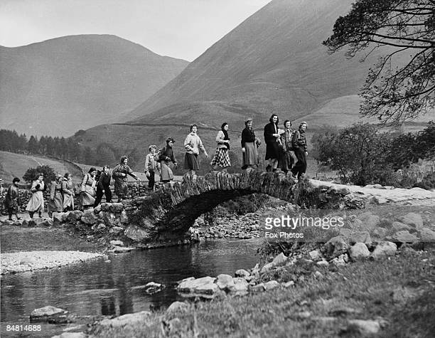Schoolgirls on an outward bound course, crossing a stone bridge over the River Irt in the Wasdale valley in the Lake District, Cumbria, October 1951.