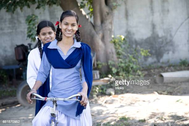 schoolgirls on bicycle - indian stock pictures, royalty-free photos & images