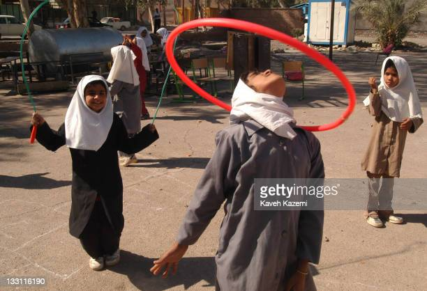 Schoolgirls play in the courtyard of their demolished school 11 months after a major earthquake struck the city Bam Iran 6th November 2004 The 2003...