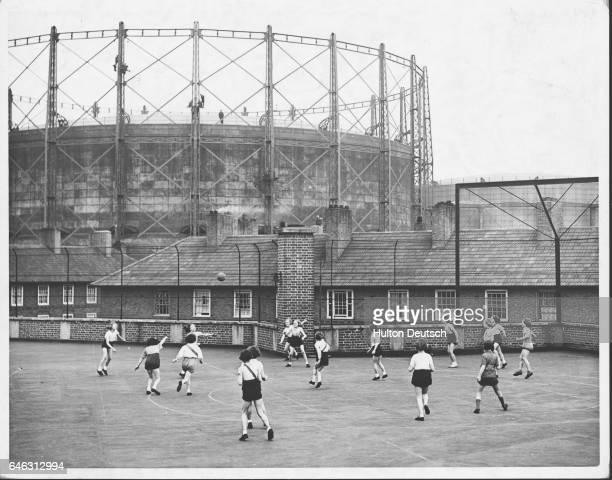Schoolgirls play netball on a rooftop playground at the Henry Fawcett School in Kennington. London, 1938. | Location: Henry Fawcett School,...