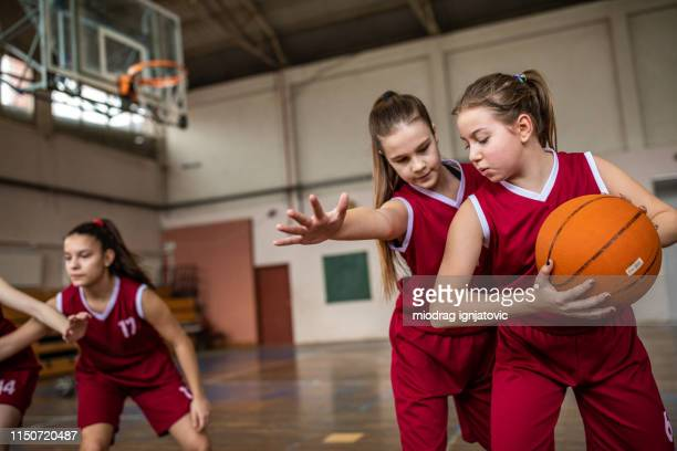 schoolgirls playing basketball in school gym - charging sports stock pictures, royalty-free photos & images
