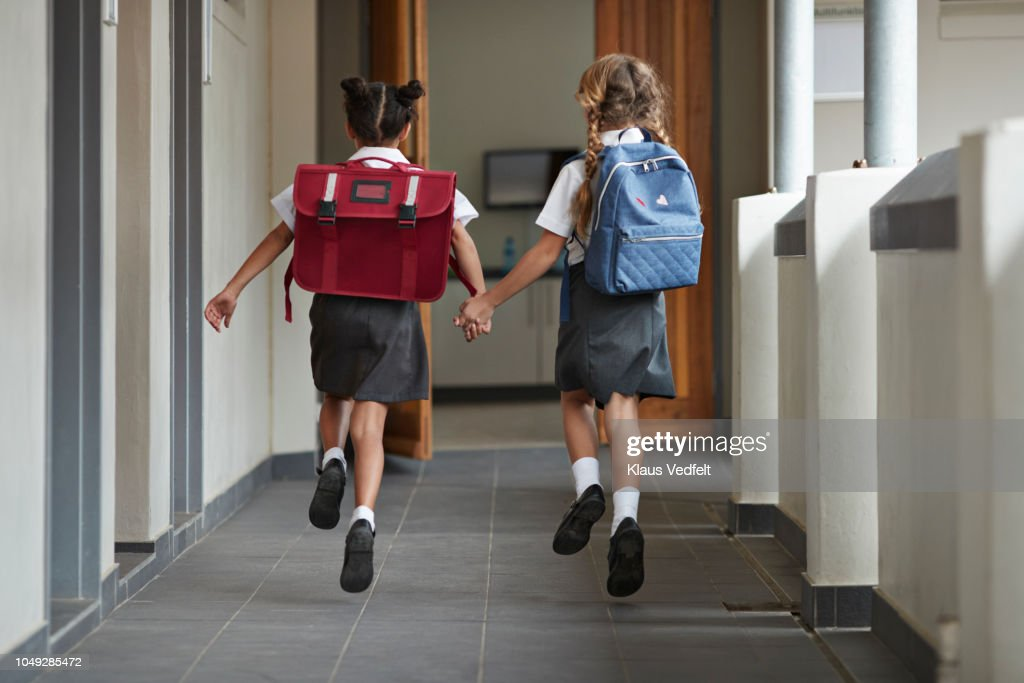 Schoolgirls running hand in hand on the isle of school and laughing : Stock-Foto