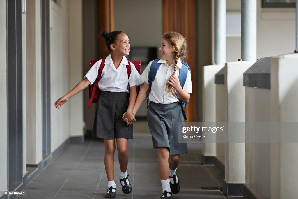 Schoolgirls running hand in hand on the isle of school and laughing : Foto de stock