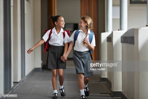 schoolgirls running hand in hand on the isle of school and laughing - seulement des enfants photos et images de collection