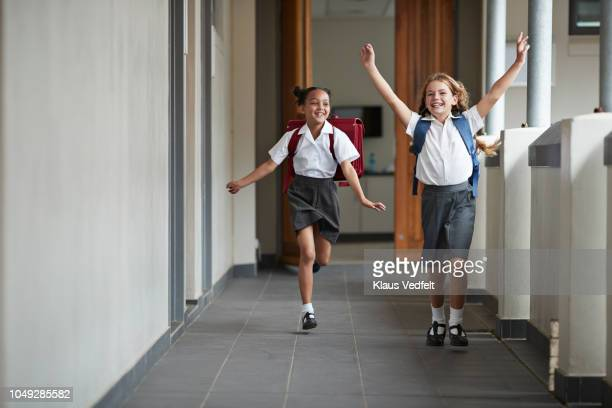 schoolgirls running in the isle of school and laughing - primary school child stock pictures, royalty-free photos & images