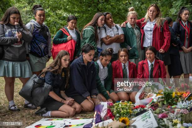 Schoolgirls sing next to flowers and tributes during a students vigil near Al Noor mosque on March 18 2019 in Christchurch New Zealand 50 people were...