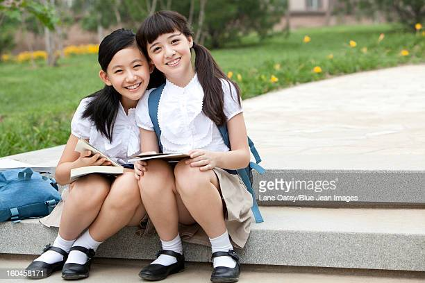 Schoolgirls sitting on steps with books smiling happily outside