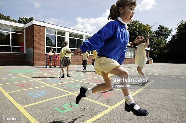 Schoolgirls skipping in a primary school playground in the UK
