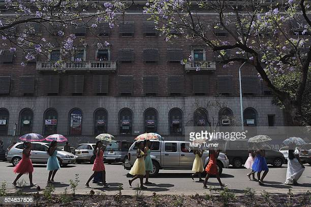 Schoolgirls take part in a small street carnival along the streets of downtown Harare Zimbabwe on October 10th 2015 There is a veneer of prosperity...