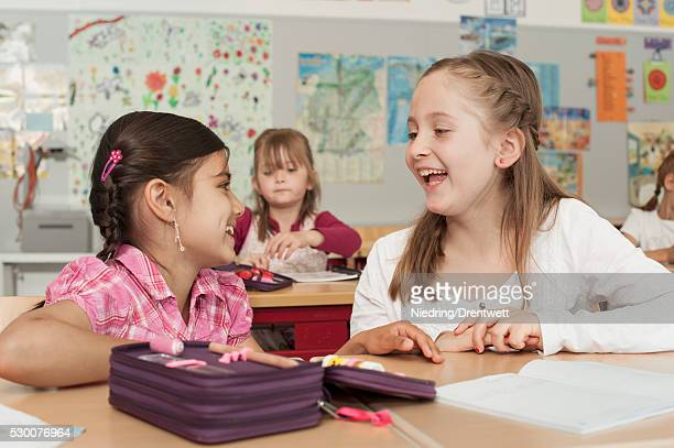 Schoolgirls talking in classroom, Munich, Bavaria, Germany
