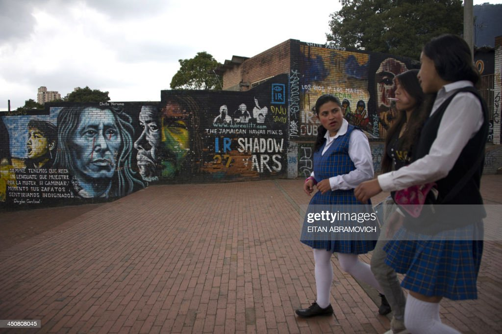 Schoolgirls walk by a graffiti in Bogota on November 19, 2013. The graffiti, once considered vandalism, is gaining more space in Bogota, with a city tour and the support of the mayor's office which provides walls, materials and fees to street artists. AFP PHOTO/Eitan Abramovich /