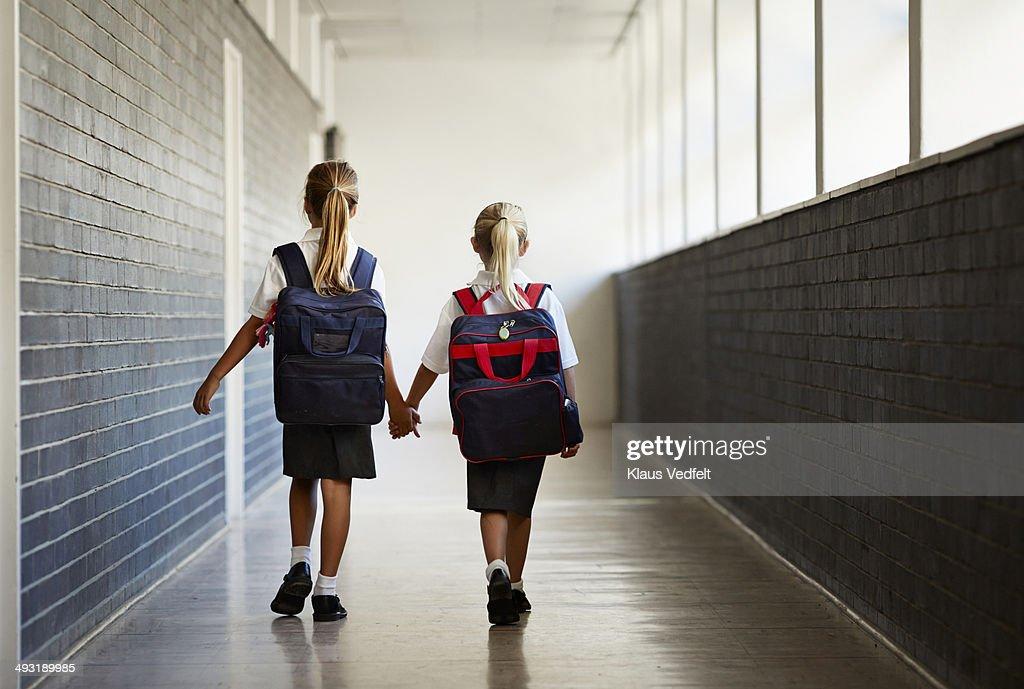 Schoolgirls walking hand in hand at school isle : Stock Photo