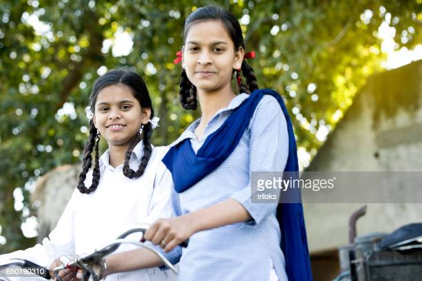 schoolgirls with bicycle - indian culture stock pictures, royalty-free photos & images