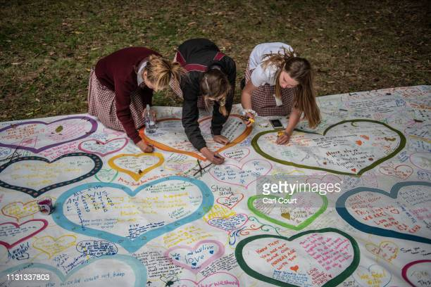 Schoolgirls write messages on a banner during a students vigil near Al Noor mosque on March 18 2019 in Christchurch New Zealand 50 people were killed...