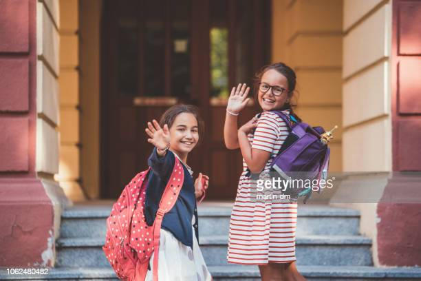 schoolkids waving with hand to their parents before entering the school building - first day of school stock pictures, royalty-free photos & images