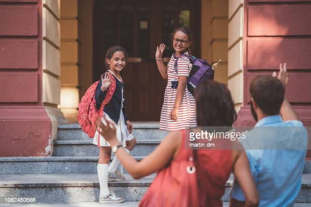 schoolkids waving with hand to their parents before entering the school building - entrata foto e immagini stock
