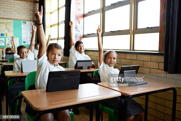 Schoolkids with raised hands in class